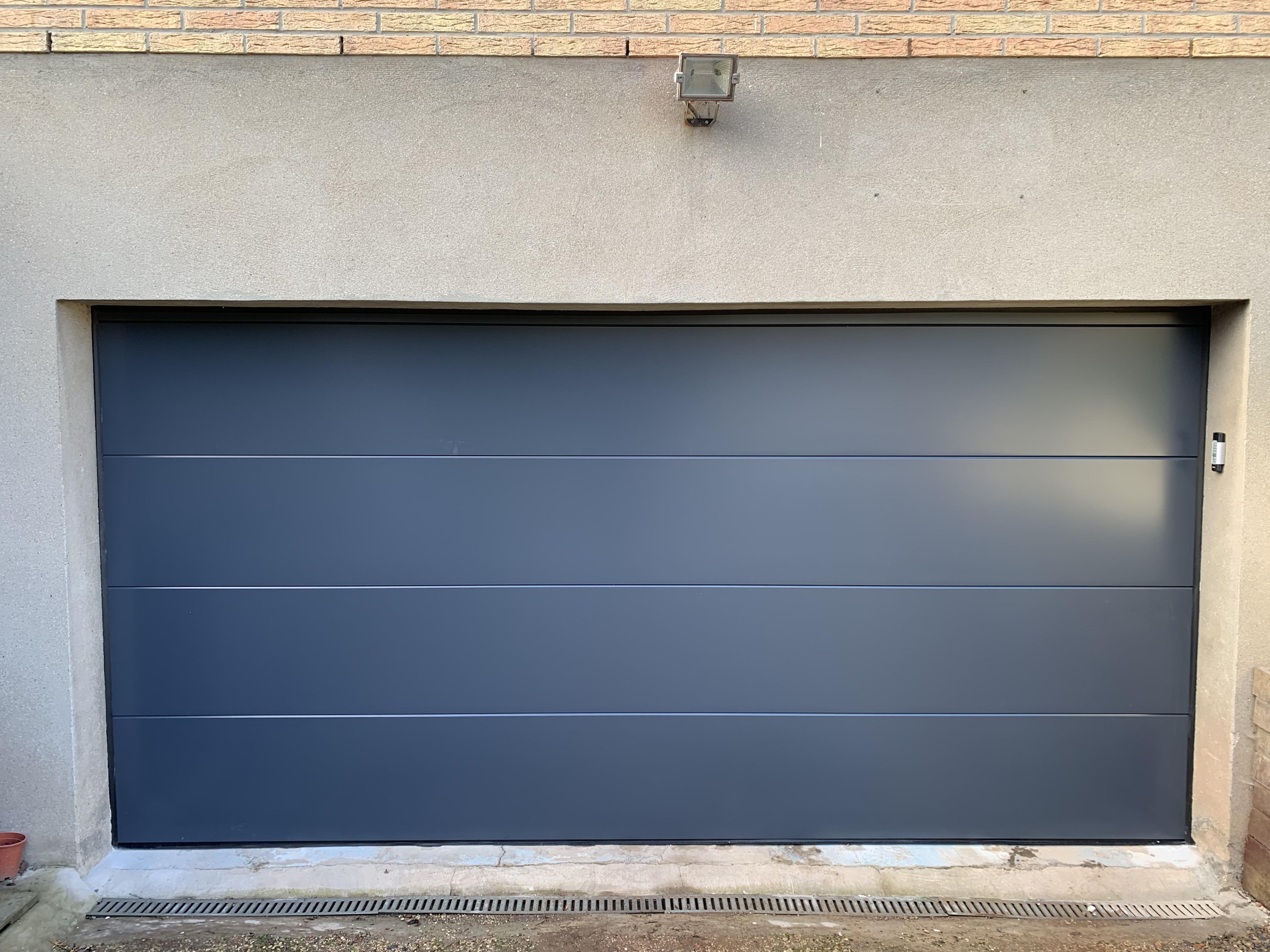 entree cimentee et porte de garage noire electrique